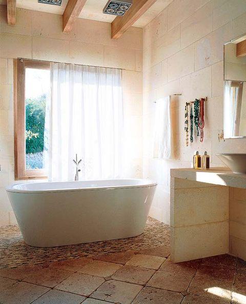 esta bañera creada por philippe starck, con grifería de hansgrohe, se convierte en el foco de atención en este baño