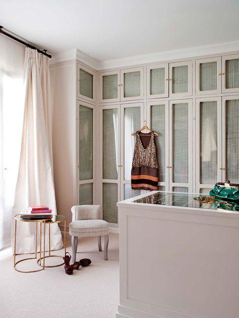 vestidor con puertas con cuarterones pero revistiéndolas con cristal y una tela a juego con la tapicería de la silla