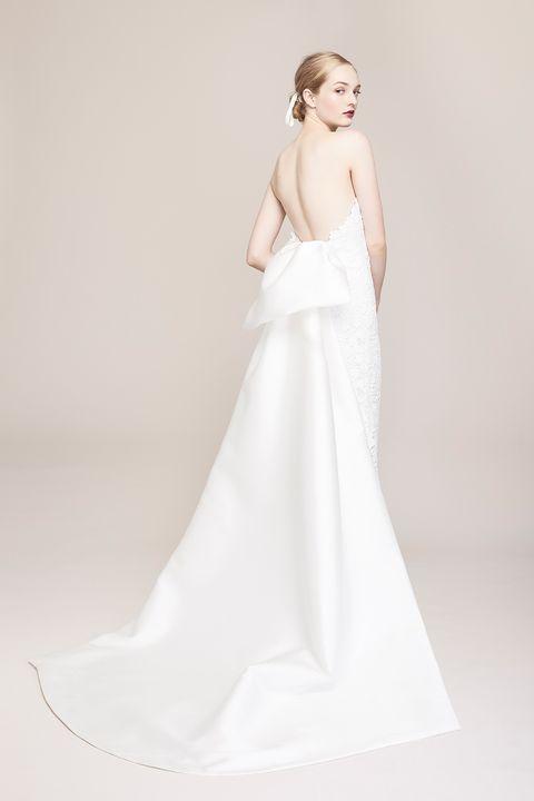 ボディはレース、トレーンはミカド素材と異なるマテリアルを組み合わせたドレス。「レラ ローズ」らしい品のあるバックスタイルです。ドレス レンタル料¥360,000(ザ・トリート・ドレッシング)