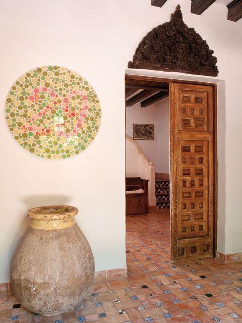 suelos de barro y un arco sobre el dintel acompañan a esta puerta policromada