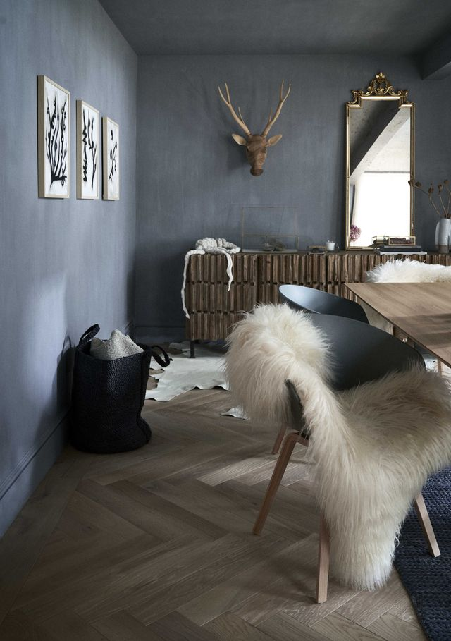 dining room, wooden dining table, black chairs with sheep skin rugs, herringbone wooden flooring, charcoal gray painted walls