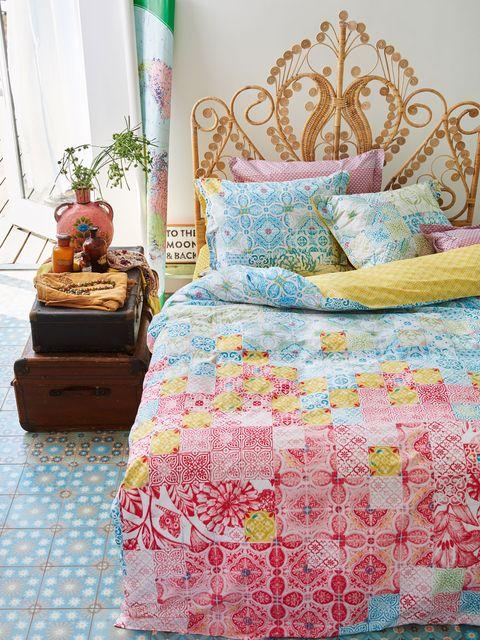 dormitorio con cabecera ornamentado de fibra y textiles coloridos