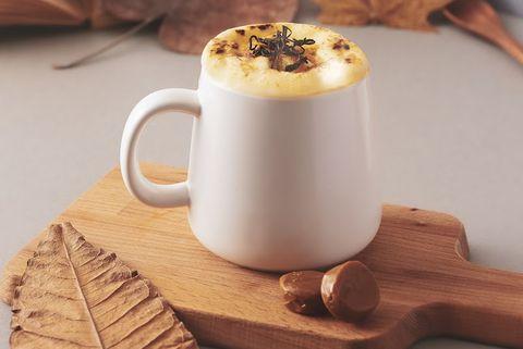 咖啡色盤子上有白色杯子裝著拿鐵