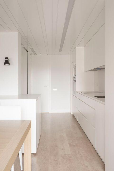 se ha unido estéticamente la cocina abierta son el salón empleando armarios blancos y de líneas sencillas en ambos espacios