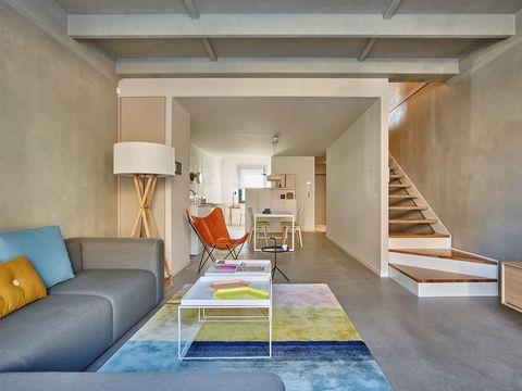 una base neutra que se altera con notas de color, con discreción cojines en el sofá, una alfombra que delimita el área y mucha sencillez