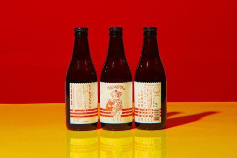 紅黃色的背景前有3罐啤酒