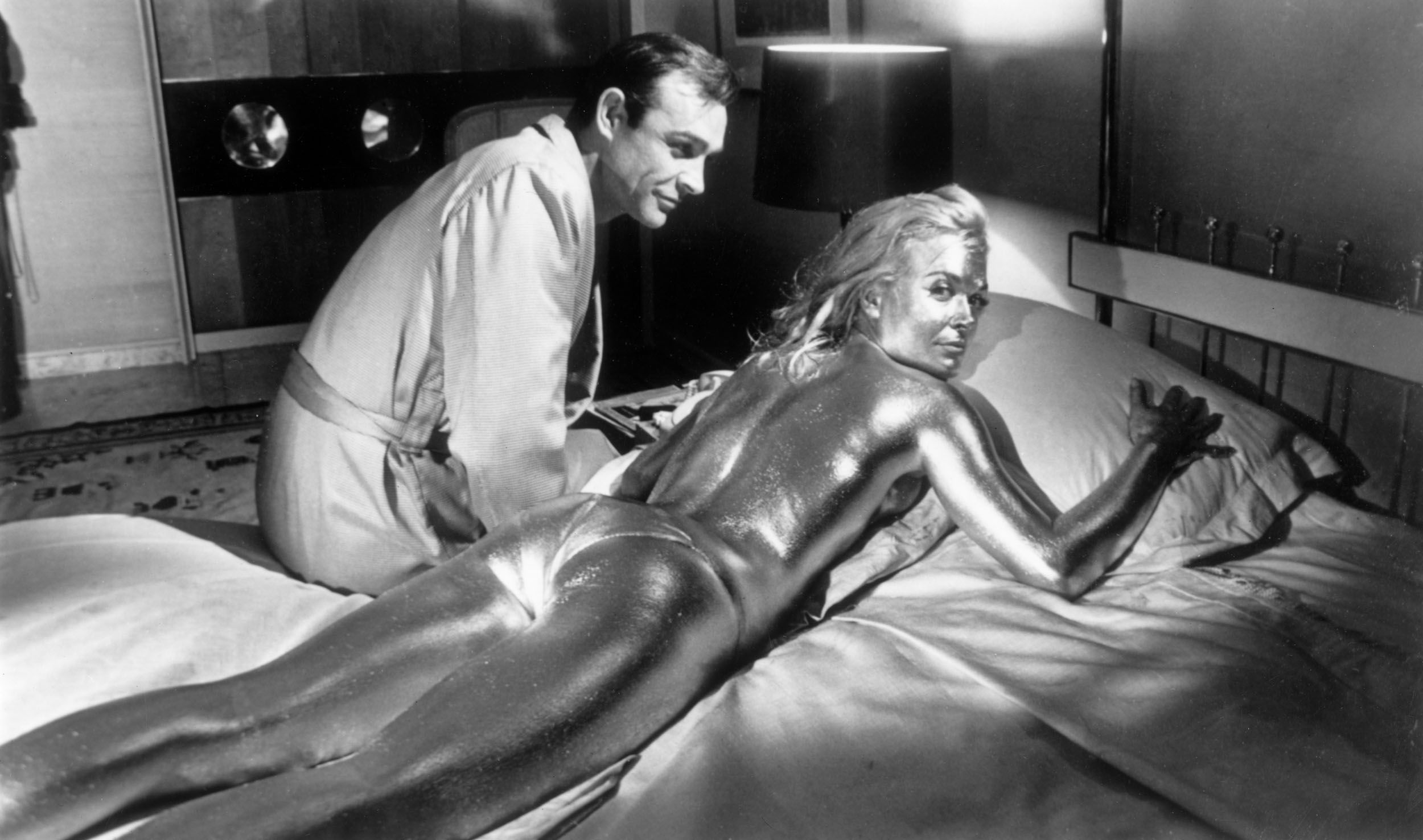 Sean Connery sitting beside his co-star English actress, Shirley Eaton, covered in gold during the filming of a scene from Goldfinger.