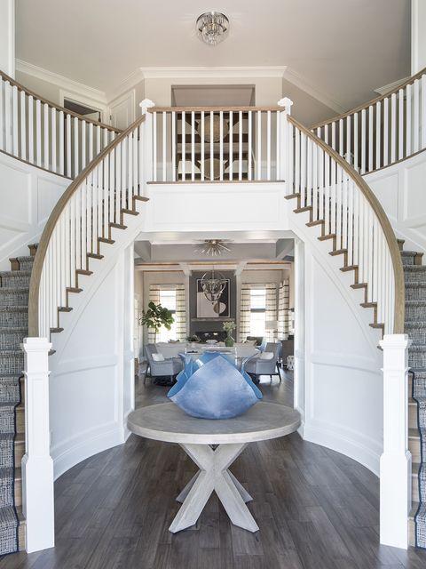 la escalera que flanquea el salón desde la entrada, se erige como una figura escultórica
