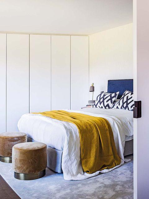 este armario lleva puertas lisas hasta el techo que simulan una pared panelada