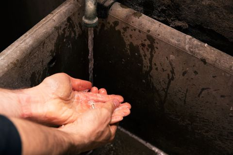 Person washing their hands in an old cement sink with soap and water.