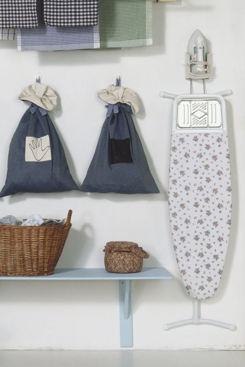 Wall space used for hanging clothes bags, drying rack and ironing board, and, underneath, baskets for washed and unwashed items and a washing machine, front view.