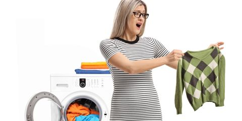 Shocked young woman holding a shrunken blouse in front of washing machine