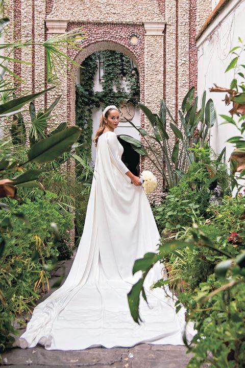 Gown, Bridal clothing, Wedding dress, Petal, Dress, Bride, Tradition, Arch, Veil, Bridal veil,