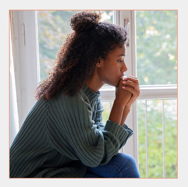 woman thinking while sitting by window alone