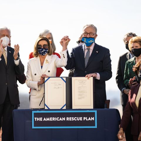 nancy pelosi and chuck schumer holding hands and celebrating the passage of the american rescue plan ac