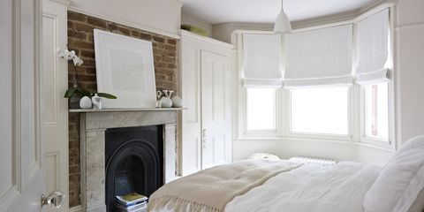Bedroom with bed, fireplace and bay window, residential house, Port Hall Street, Brighton, East Sussex, UK