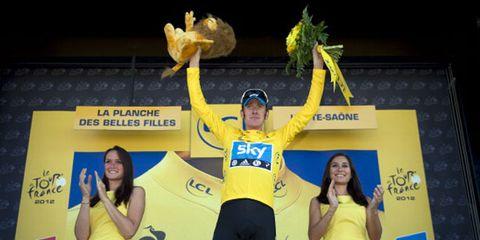 Yellow, Sports uniform, Logo, Award ceremony, Spandex, Podium, Cycling shorts, Cheering,