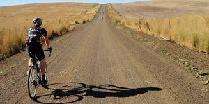 man on bike riding on long gravel road