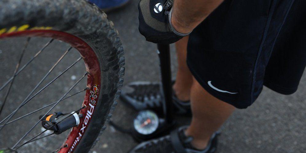 Man pumping bike tire with floor pump