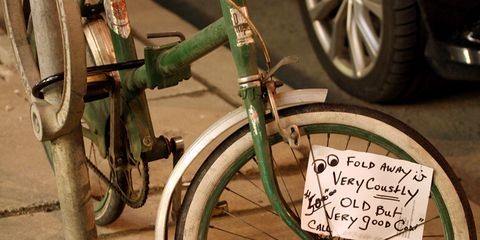 used bike for sale on sidewalk with sign