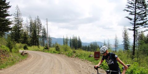 Cyclist stretching leg muscles on a forest trail