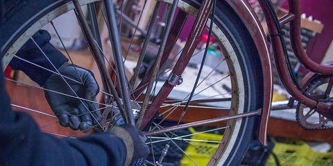 bike mechanic working on bike wheel