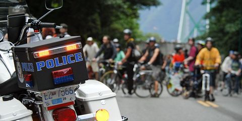 A police scooter in front of cyclists.