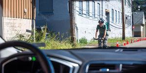 A cyclist passes a pilot model of the Uber self-driving car