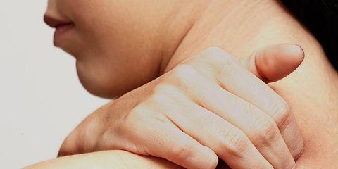 woman rubbing shoulder