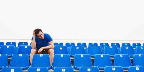 man sitting in empty bleachers procrastinating workout