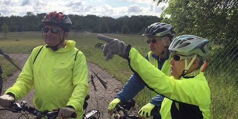 Cyclists Bob Strader, left, of Texas Township, and Carolyn and Bill Burns from Portage, stop by the scene on June 8, 2016 morning to pay respects on North Westnedge Avenue north of Kalamazoo after five cyclists were killed and four were injured Tuesday ni