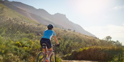 Cyclist riding a dirt road on the side of a mountain