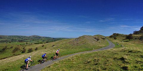 three road cyclists climbing a hill