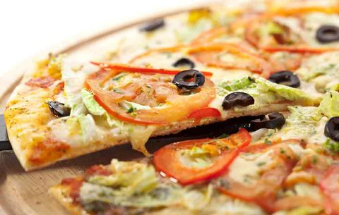 a thin crust pizza with olives and tomatos