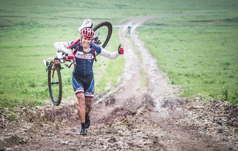 man carrying bike through mud
