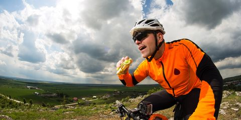 A cyclist eating healthier fast food options on a bike.