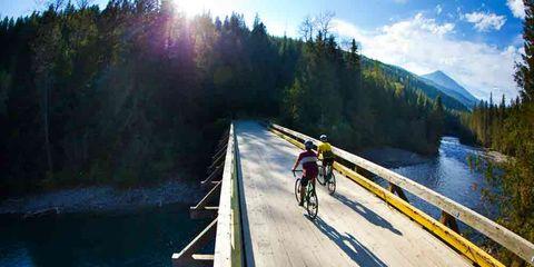 cyclists riding over a flat bridge