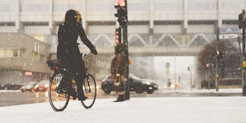 woman cycling in snowy city