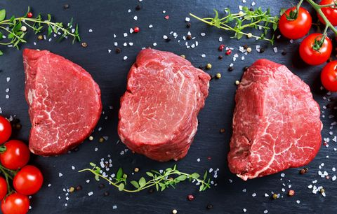 a trio of filets on a black countertop with salt and herbs strewn about
