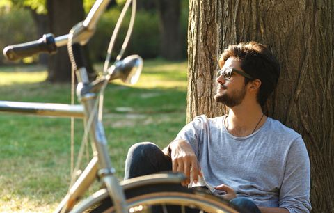 man relaxing near a tree