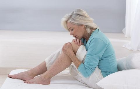 woman sitting on bed holding her leg