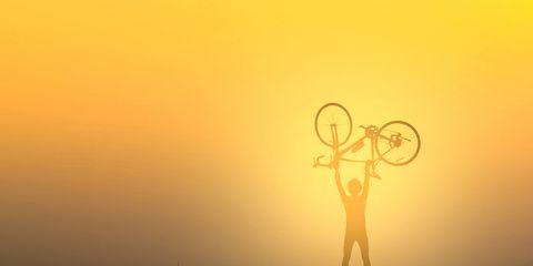 cyclist lifting bike
