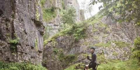 cyclist taking a break on a spring mountain road