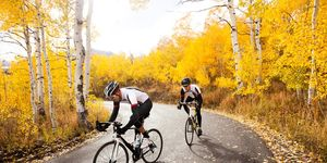 Two cyclists riding in the fall