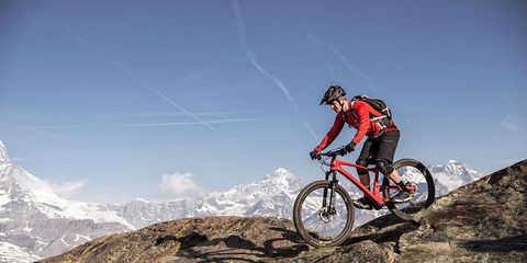 Rider on DT Swiss XRC 1200 Spline 25 wheels riding on boulders with mountains in the background