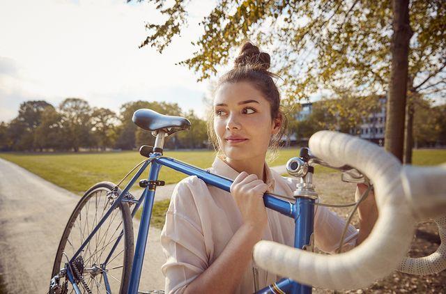 vrouw tilt fiets in park