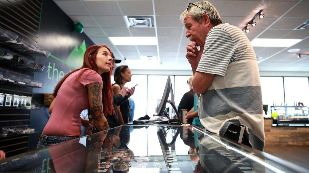 Ariel Conley, a bud tender at the Dispensary in Reno, waits on a customer on the first day of recreational marijuana sales.