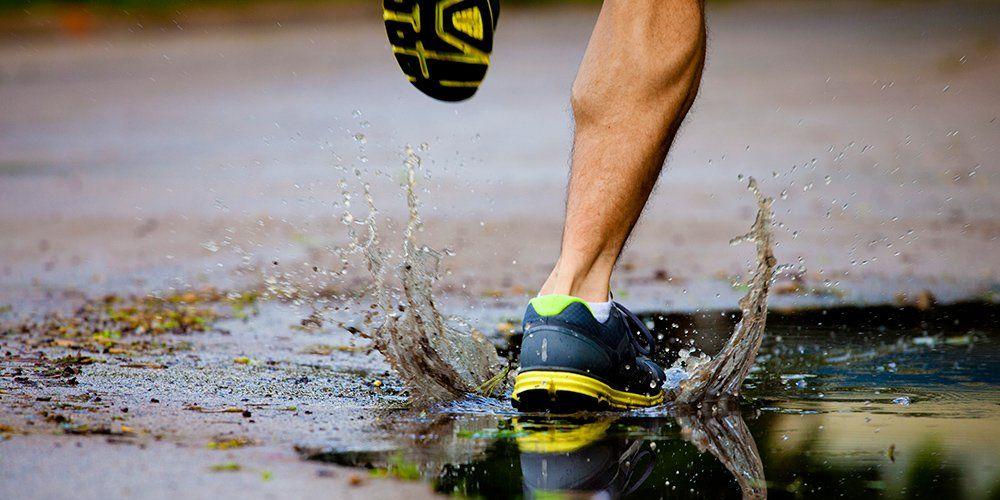 man's foot running, splashing in a puddle