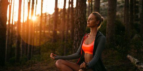Women meditating in forest