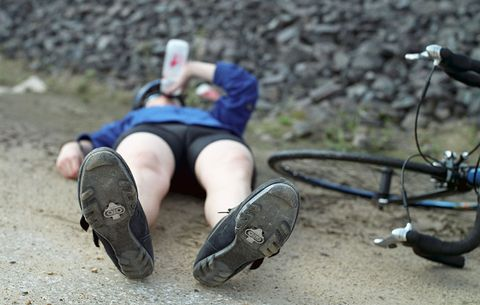bicyclist drinking while lying on ground